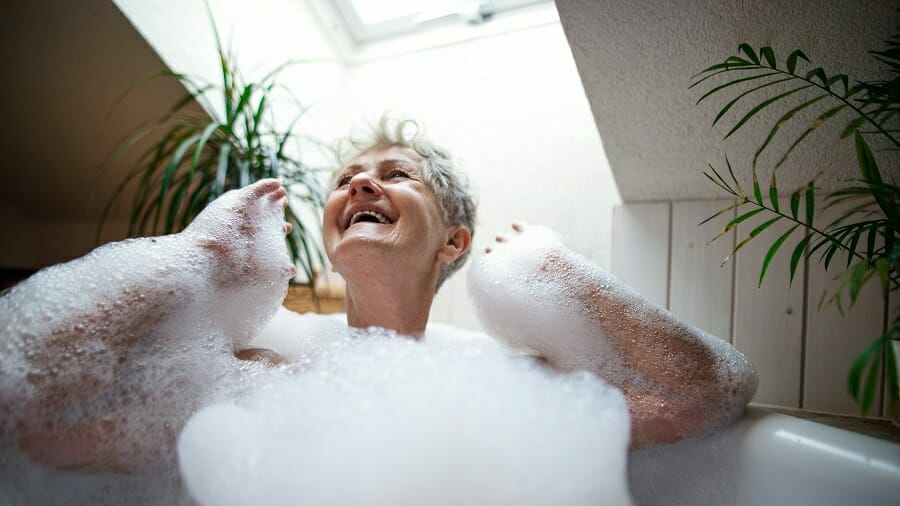 Cheerful senior woman washing in a bubble bath